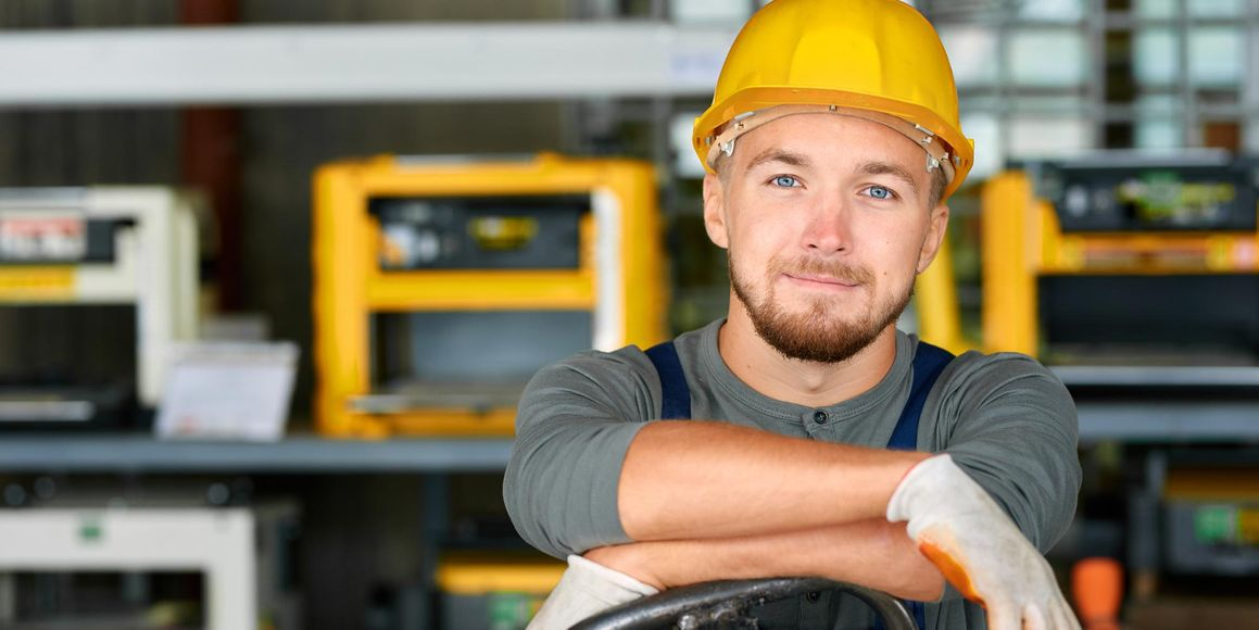 Hirdes & Partner Rechtsanwälte in Braunschweig, Portrait of cheerful young worker wearing hardhat posing looking at camera and smiling enjoying work at modern factory